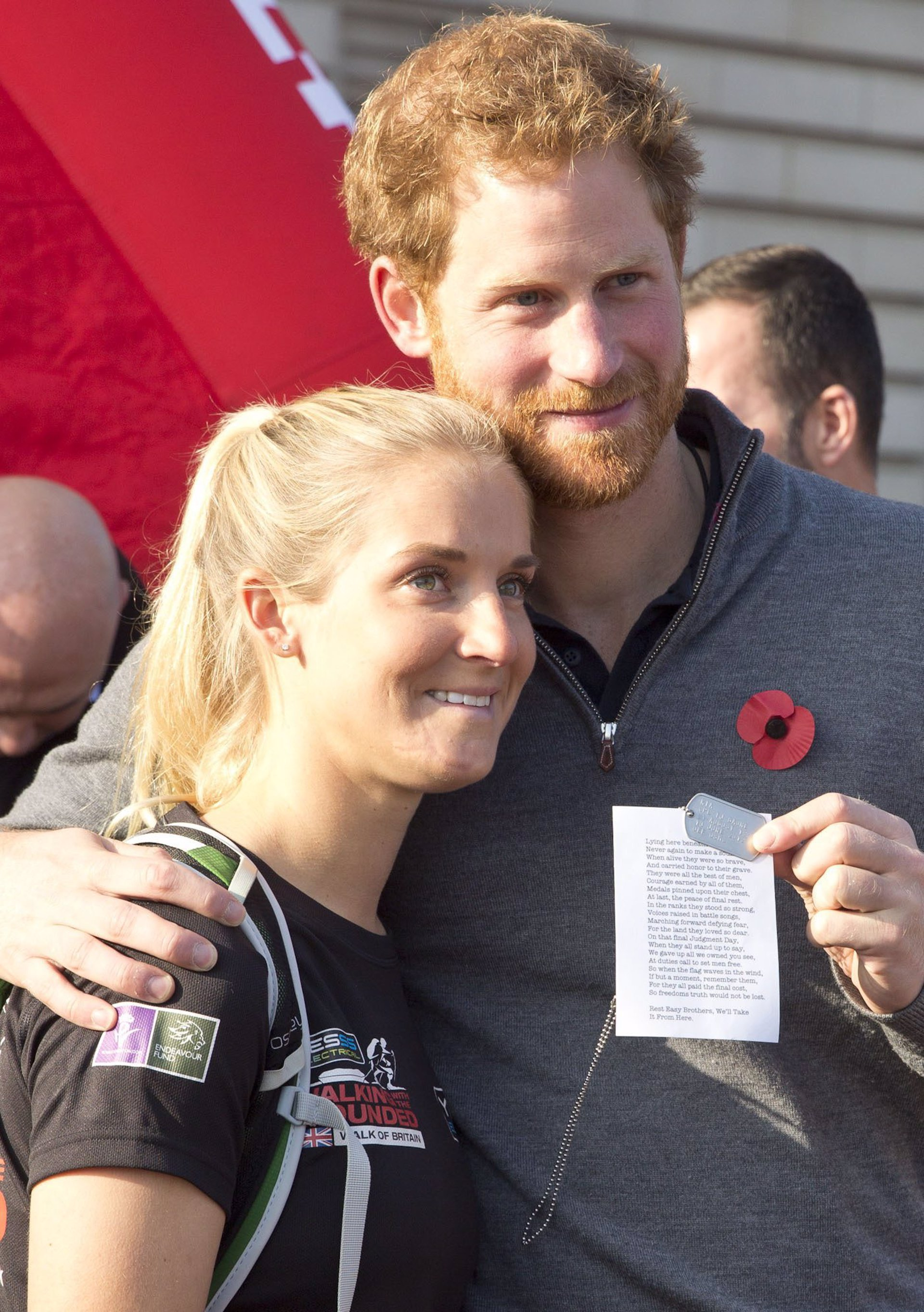 El príncipe Harry con Kristie Ennis, mostrando la chapa del cabo Baune