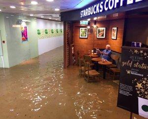 Un hombre permanece impasible ante una inundación en un starbucks de Hong Kong